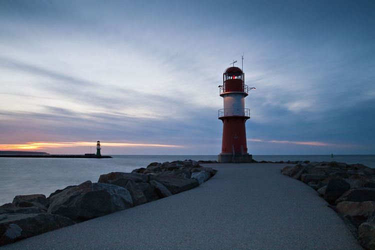 Mole in Warnemuende, Germany. Architecture Baltic Sea Building Exterior Built Structure Calm Cloud Dusk Idyllic Lighthouse Mole Nature Outdoors Protection Rock - Object Rostock Safety Sea Security Shore Sky Sunset Tower Tranquil Scene Warnemünde Water