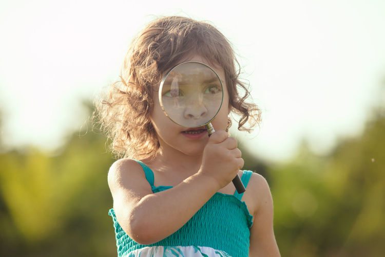 Cute girl holding magnifying glass outdoors