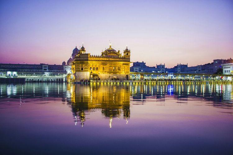Illuminated harmandir sahib against clear sky during sunset