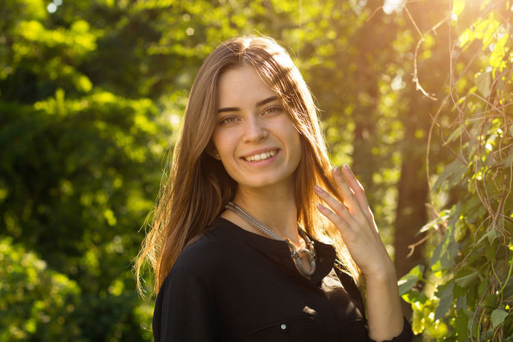 Young woman touching her hair Outdoors Hairstyle Nature Beautiful Woman Women Plant Beauty Adult Tree Headshot Looking At Camera Young Women Sunlight Long Hair Young Adult Hair Emotion Portrait One Person Happiness Smiling Real People Leisure Activity Lifestyles