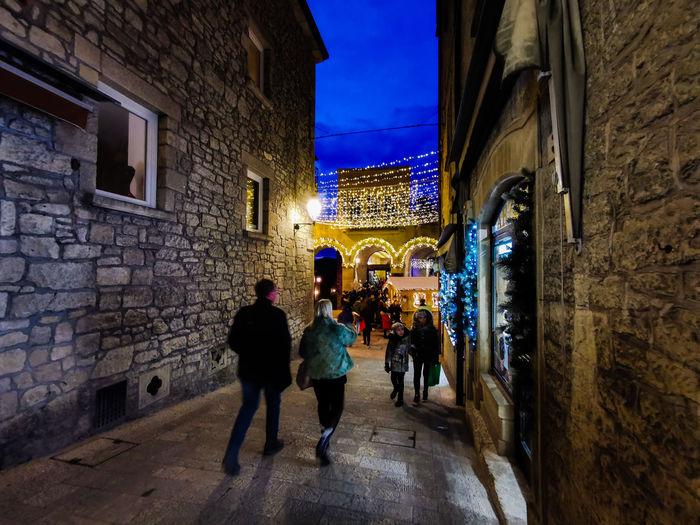 People walking in alley amidst buildings at night
