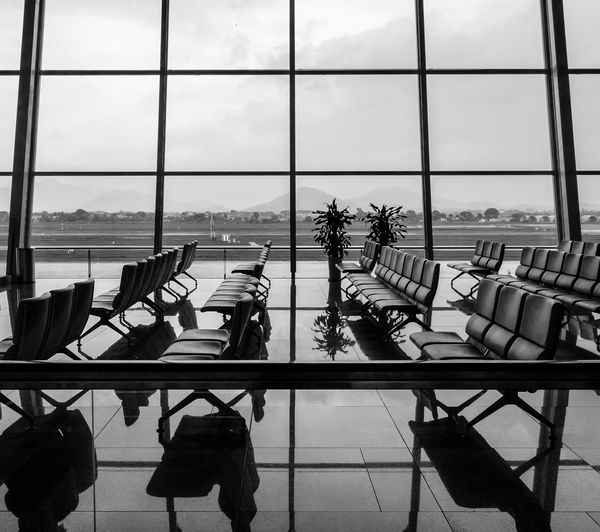 airport Tiled Floor Airport Terminal Glass Modern Arrangement Empty Travel Reflection Transportation Nature Sky Airport Departure Area Flooring Day No People Table Airport Chair Seat Indoors  Transparent Glass - Material Window Airport Runway Airportphotography