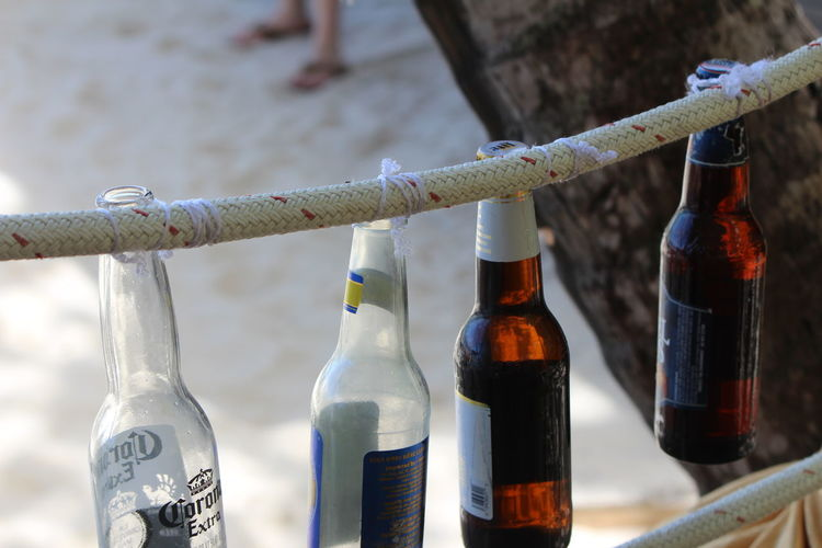 High angle view of beer bottles hanging from rope