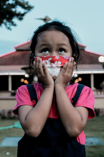 Portrait of girl standing outdoors wearing the mask