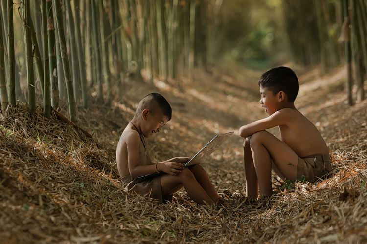 Asian two boys playing laptop at Countryside,Finding Notebook Computer Knowledge in Rural Asia. Boys Child Childhood Day Full Length Innocence Land Leisure Activity Lifestyles Males  Men Nature Outdoors People Plant Real People Shirtless Side View Sister Sitting Togetherness Two People