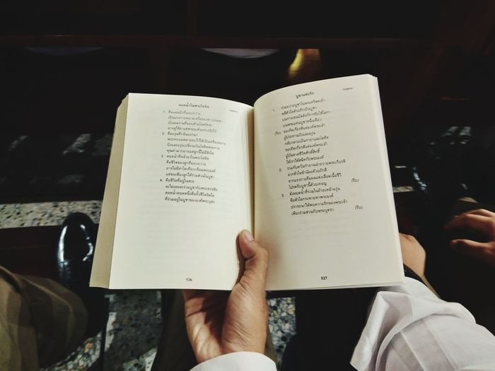 Midsection of person holding book