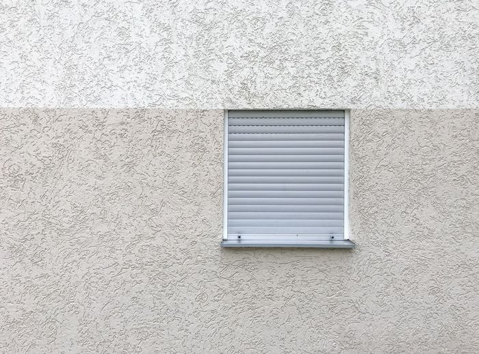 Low angle view of window on white wall