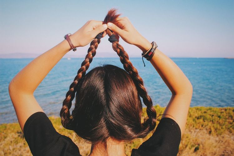 Rear view of young woman holding braided hair against sea