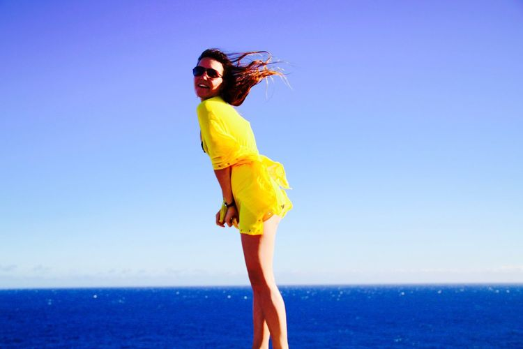 Side View Of Happy Woman In Yellow Top Standing At Beach Against Sea And Sky On Sunny Day