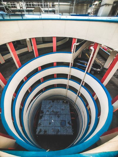 Spiral carpark at Chinatown Red And Blue Car Spiral Carpark Spiral Chinatown Singapore IPhone Architecture Built Structure Day No People Building Exterior City Multi Colored Spiral High Angle View Circle Geometric Shape Mode Of Transportation Transportation Outdoors The Architect - 2018 EyeEm Awards