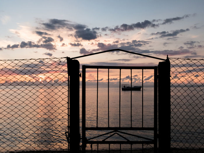 Silhouette Gate By Sea Against Sky During Sunset