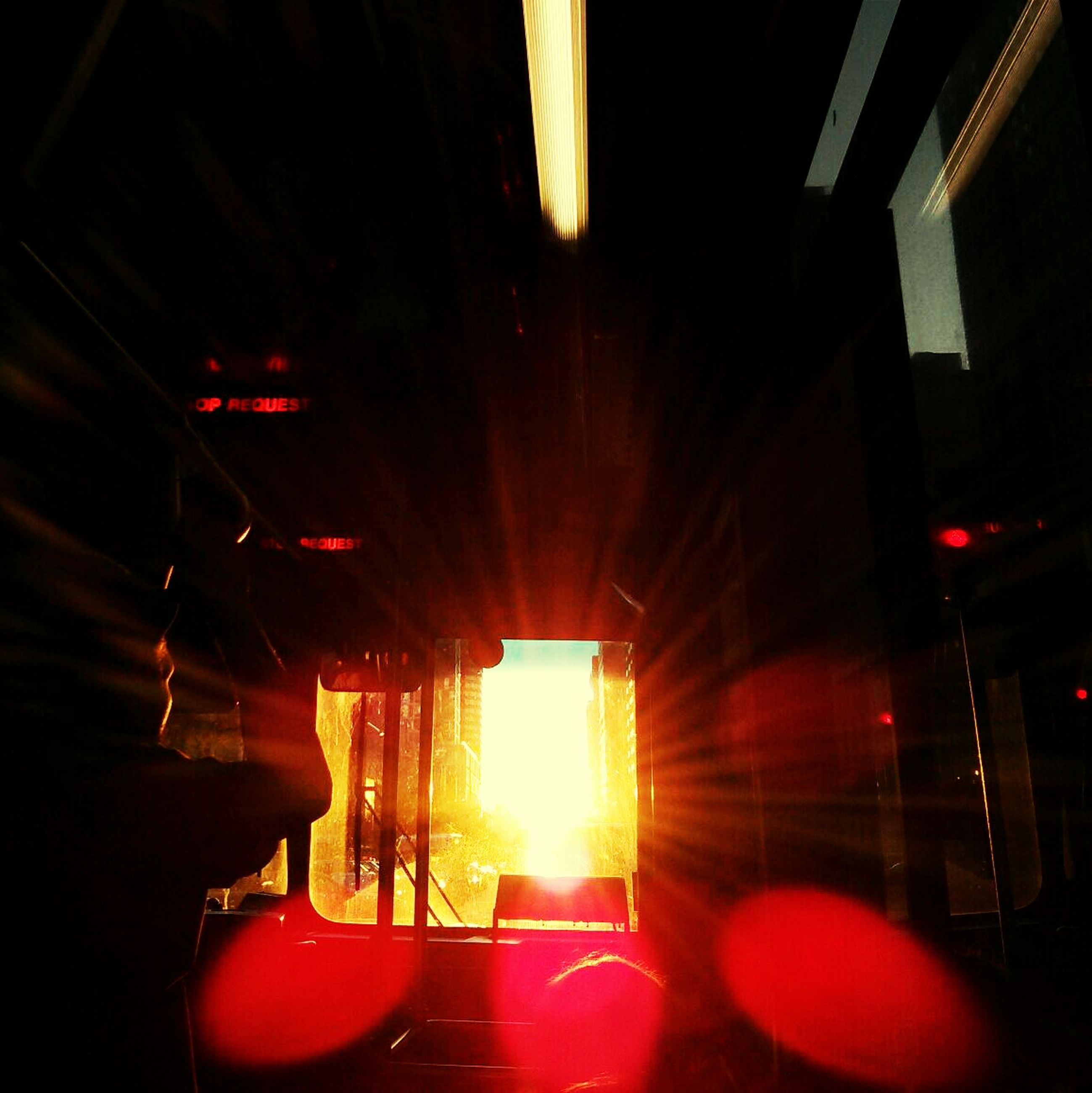 indoors, illuminated, lighting equipment, transportation, ceiling, dark, night, interior, built structure, sunlight, low angle view, architecture, light - natural phenomenon, window, no people, glowing, mode of transport, glass - material, in a row, hanging