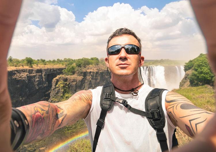 Portrait Of Man Wearing Sunglasses Against Waterfall