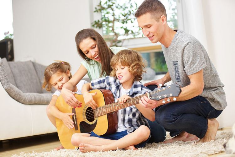 Happy Family Playing Guitar In Living Room At Home