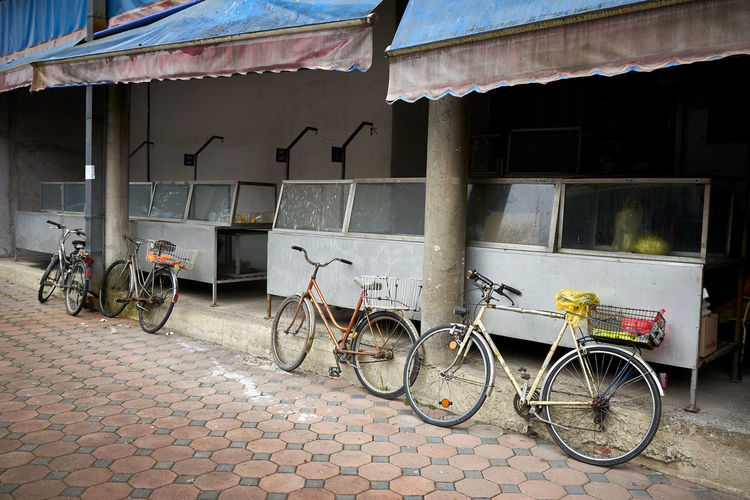 Bicycles parked on street against old building