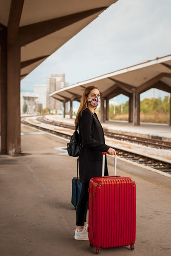 Young woman wearing mask standing on railroad station platform