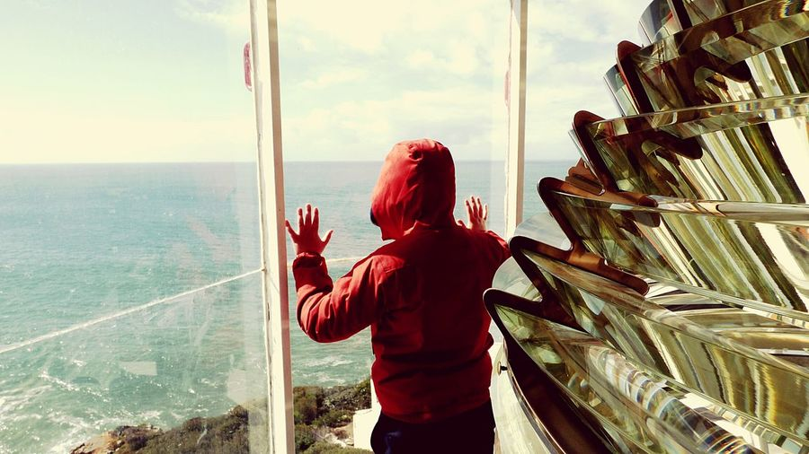 The Boy on the Lighthouse Looking To The Sea Scenicview On The Lighthouse Showcase March Sea View Hight Point Scenic View Red Windbreaker People Real People Sea Sky Seaside_collection Lighthouseview Lighthouse_captures Young Boy Seaview Sea_collection On The Lighthouse Looking Down Red Ocean View Landscapes With WhiteWall