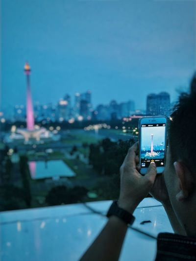 Cropped Image Of Man Photographing Illuminated National Monument In City At Dusk