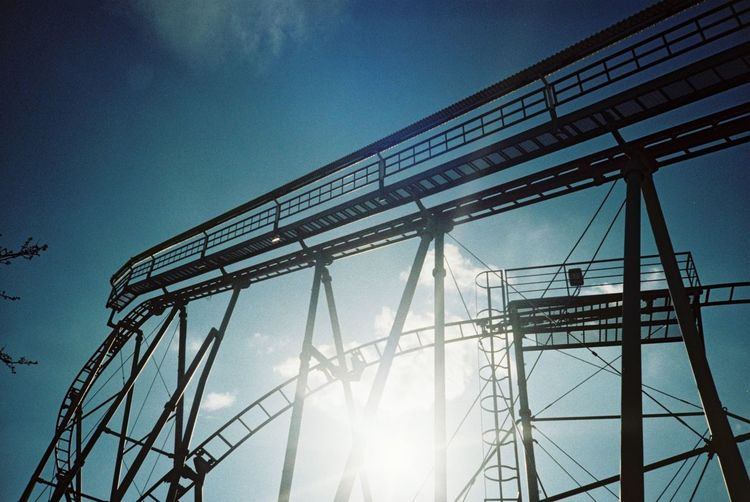 Low Angle View Of Silhouette Rollercoaster Ride Against Sun In Sky