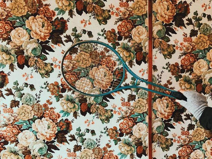 Cropped Hand Holding Racket By Floral Pattern Wall