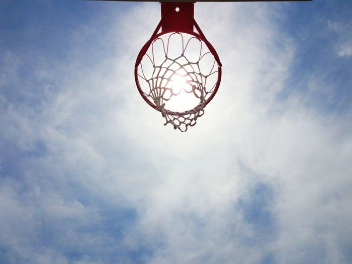 Low angle view of basketball hoop against cloudy sky during sunny day