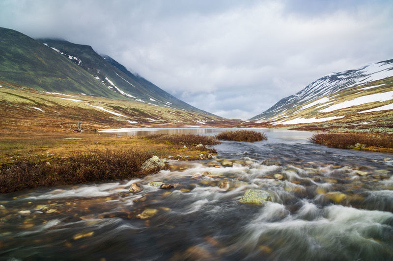 Scenic view of river flowing by mountain against sky