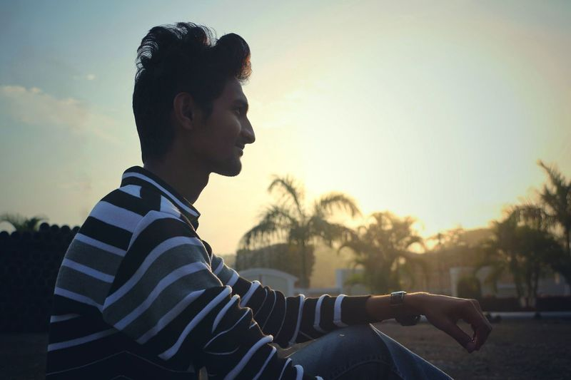 Side view of young man looking away against sky during sunset
