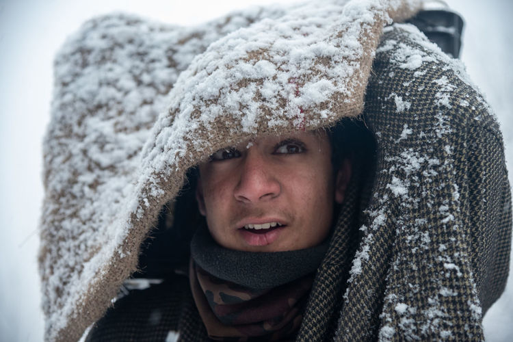 Close-up portrait of man in snow