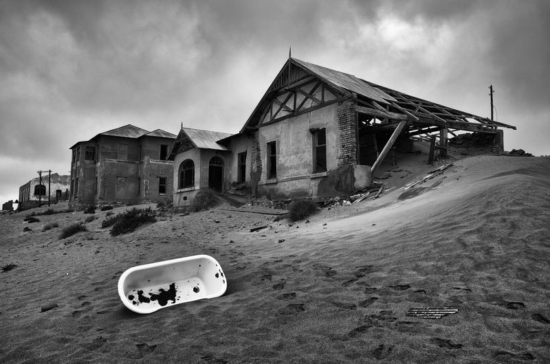 Deserted houses in Kolmanskop, Namibia Abandoned Architecture Bad Condition Bathtub Black And White Building Exterior Cloud - Sky Cloudy Damaged Deterioration Ghost Town House Kolmanskop Monochrome Photography No People Outdoors Ruined Weathered Footsteps The Architect - 2017 EyeEm Awards The Street Photographer - 2017 EyeEm Awards The Traveler - 2018 EyeEm Awards