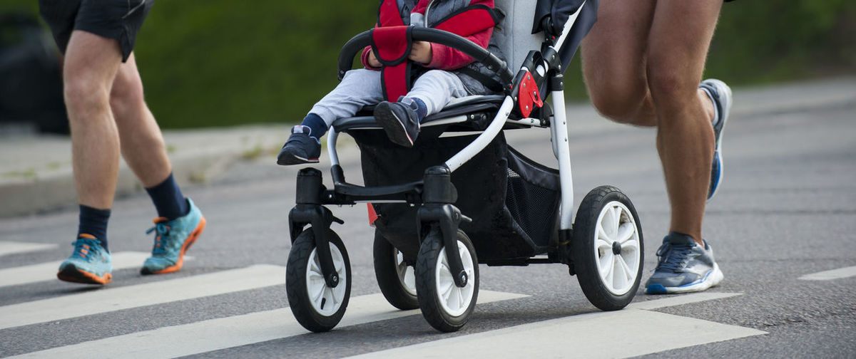 Low Section Of Man With Baby In Stroller Running On Road During Marathon
