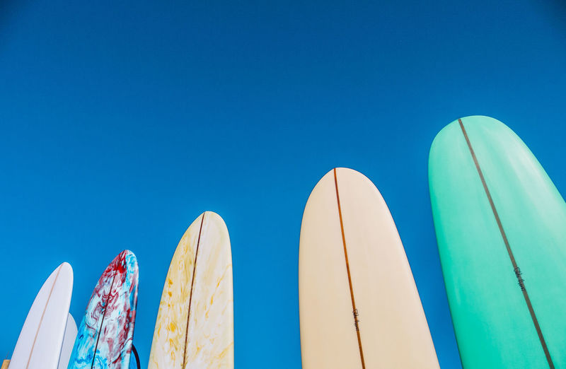 Low angle view of surfboards against blue sky