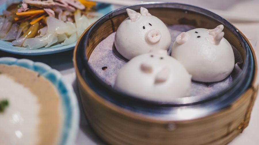 Close-up of pig shape dumplings in container on table
