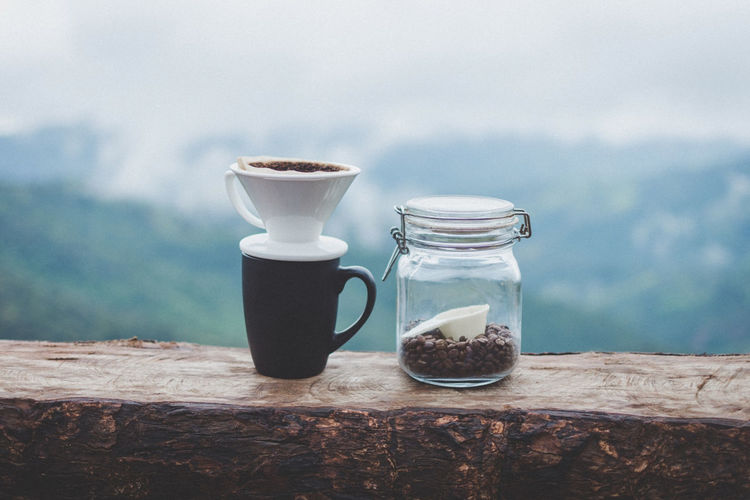 Close-Up Of Filtered Coffee In Mug By Jar On Table