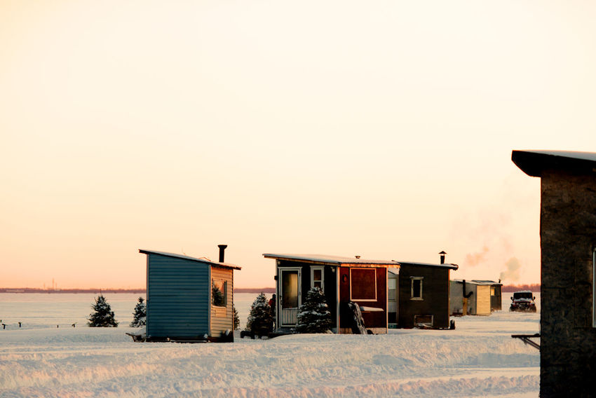 Little huts, smoking chimney and trees on a frozen lake, perfect for ice fishing. Frozen Lake At Sunset Architecture Building Exterior Built Structure Clear Sky Cold Temperature Day Ice Fishing Huts In Background Ice Fishing Huts On Frozen Lake At Sunset Nature No People Outdoors Scenics Sky Snow Sunset Winter