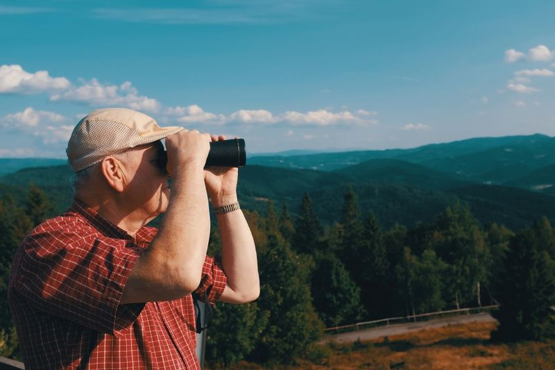 Midsection of man photographing on mobile phone against mountains