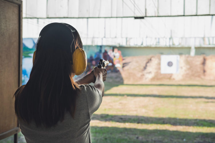 Rear view of woman aiming gun at target shooting range