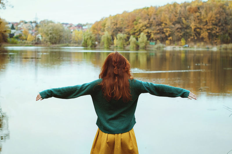Autumn rear view of redhead woman standing in lake