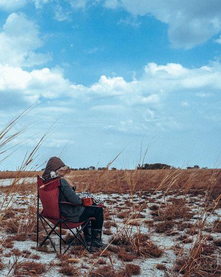 Woman on folding chair on landscape in winter