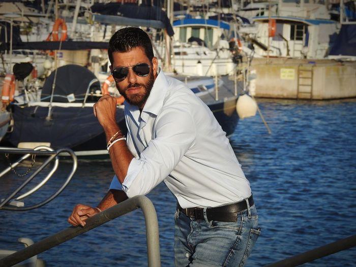 Man wearing sunglasses standing at harbor