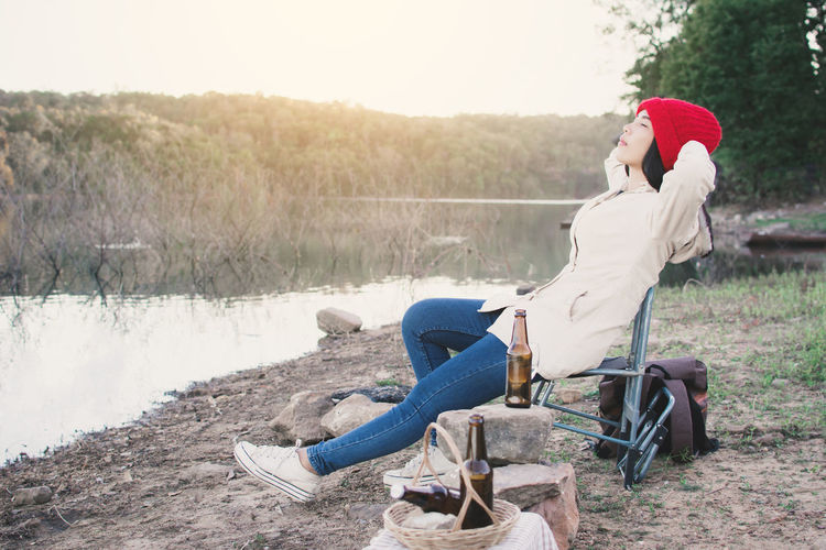Side View Of Woman Sitting On Folding Chair By Lake
