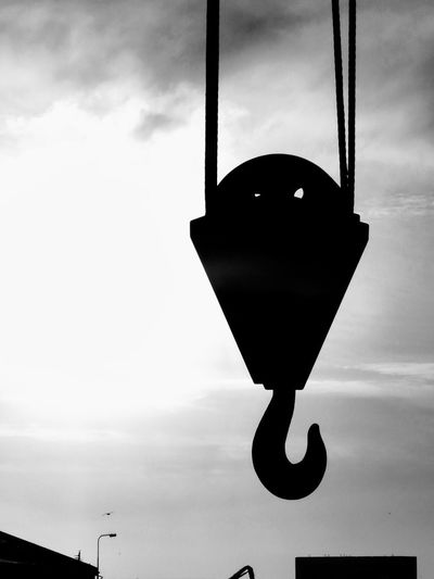 Low angle view of silhouette hanging against sky at sunset