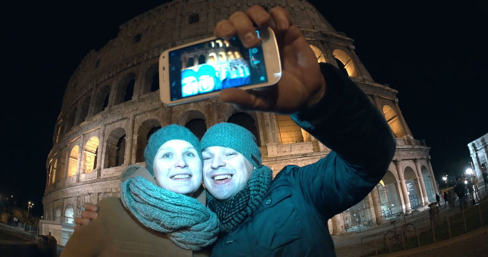 Low angle portrait of woman photographing illuminated smart phone at night
