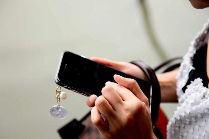 Low section of woman holding smart phone