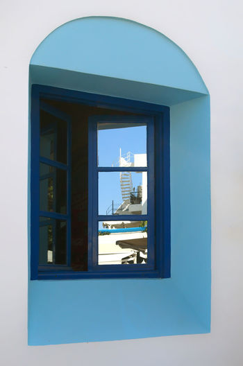 a modern white hotel building reflected in a traditional greek house window Reflection Architecture Blue Building Building Exterior Built Structure Clear Sky Copy Space Day Geometric Shape Glass - Material Greece Kos Nature No People Outdoors Reflection Sky Sunlight Transparent Vacation Wall - Building Feature Window Window Frame