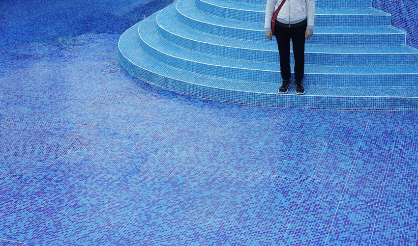 Low section of man standing on steps of empty swimming pool