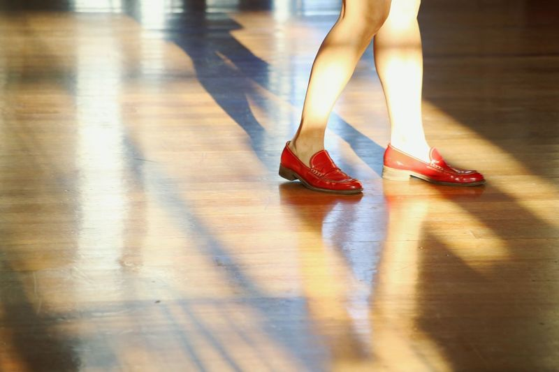 Low section of woman wearing red shoe standing on hardwood floor