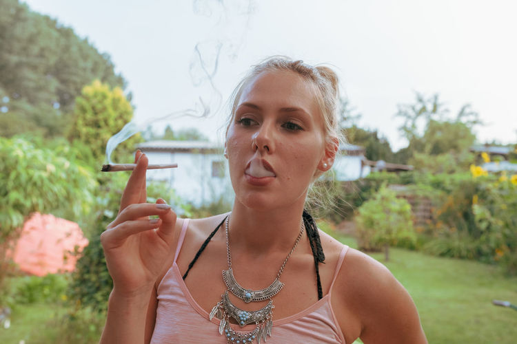 Young woman smoking marijuana joint while standing outdoors