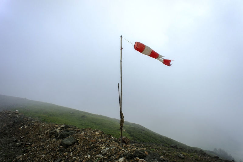 Red flag on mountain against sky
