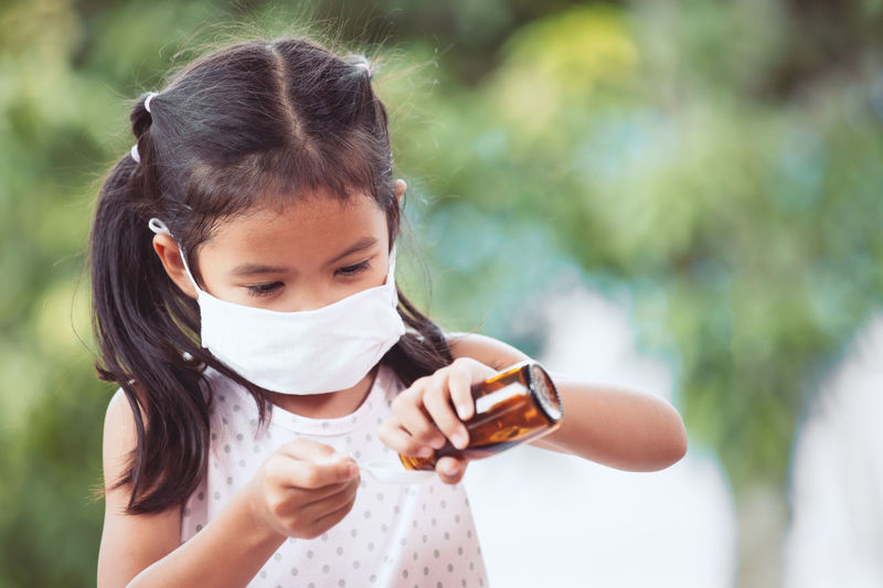 Girl wearing surgical mask while pouring dose in spoon