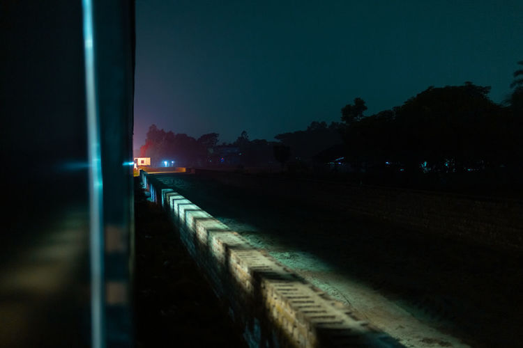 Illuminated footpath against sky at night